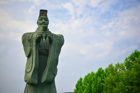 huang: A stone statues of Qin Shi Huang, holding the glass, in the blue sky is very powerful