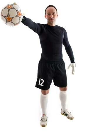 Football goalkeeper in black blouse and shorts wearing goalie gloves. Man is holding ball in right hand. Studio shot on white background.  Stock Photo