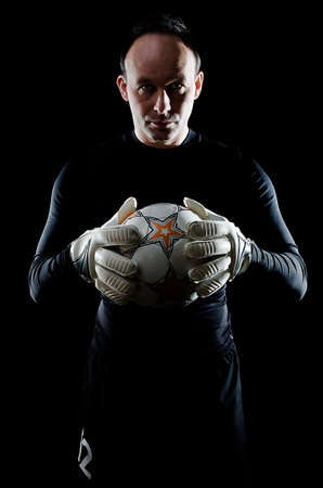 goal keeper: Portrait of football goalkeeper on black background. Man is wearing goalie gloves and goalkeeper Stock Photo
