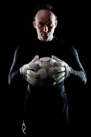 goal keeper: Portret van voetbal doelman op zwarte achtergrond. Man draagt keeper handschoenen en doelman Stockfoto
