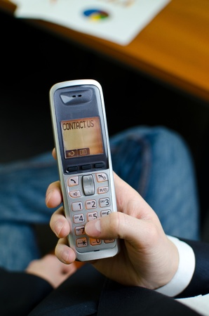 Cordless telephone with Contact us word on display, holded by businessman photo