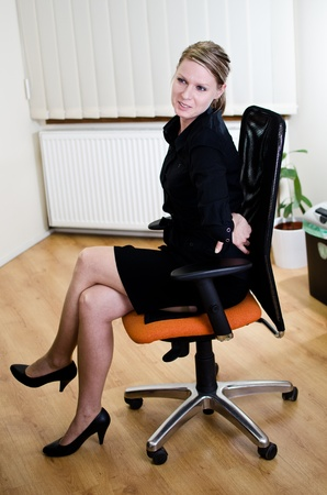 uncomfortable: Business Woman is feeling back pain sitting on office chair
