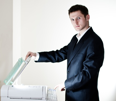 Young businessman is doing documents copies on copying machine in his office photo