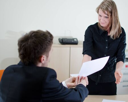 Young businessman is giving some documents to his secretary Stock Photo