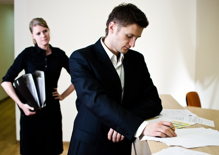 businessman signing documents: Office life scene. Young businessman signing documents and young secretary with file binders in hand. Stock Photo