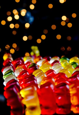 Army of sweet colorful jelly teddies with blinking lights on black background Stock Photo