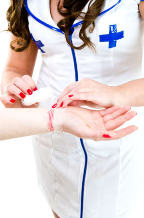 sexy nurse: Sexy nurse in uniform bandaging hand after accident
