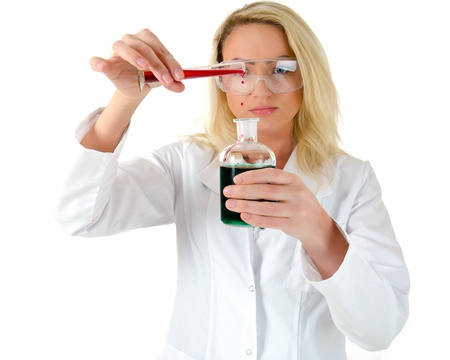 Blond woman in white coat mixing colorful liquids in a glass photo