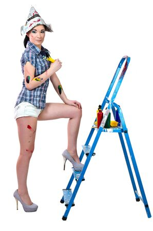 Sexy woman painter in high heels shoes wiht ladder isolated on white background photo