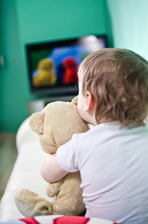 flat screen tv: Kid with teddy bear watching TV