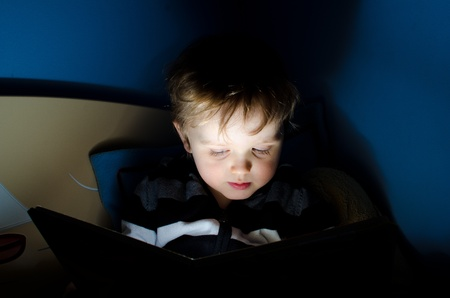 Child during reading book in his room at night