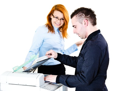 Young office workers doing copies on photocopier and flirting Stock Photo - 12586342