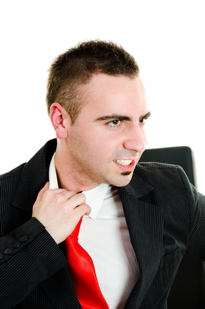 Stressed young businessman yanking necktie in frustration photo