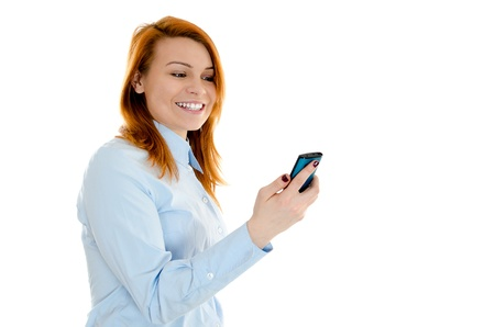 Young redheaded businesswoman smiling while reading message on her smartphone Stock Photo - 12586454