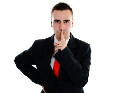 Businessman holds a finger to his lips, saying Its a secret