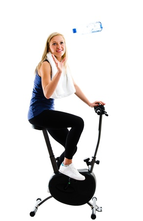 Slim blonde girl catching a bottle of mineral water or other drink while training on exercise stationary bike  photo