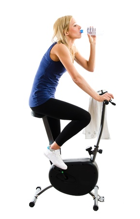 Slim fitness girl drinking mineral water while riding on a training exercise bike photo