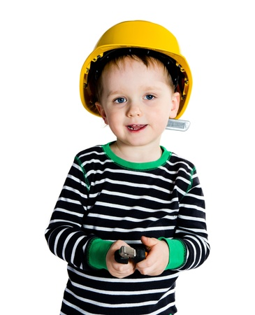 Happy smiling 2-3 years old boy in yellow helmet playing with pliers - isolated on white background photo