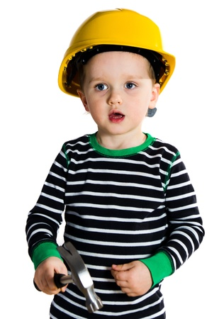 Funny little child in yellow helmet playing with hammer photo