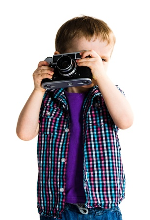 Cute child playing with retro analogue photo camera - isolated on white background Stock Photo