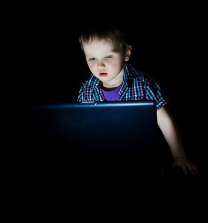 Little kid using laptop by night