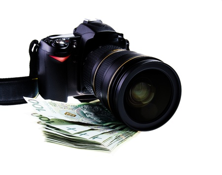 Professional dslr digital camera with zoom lens lying on stack of Polish money photo