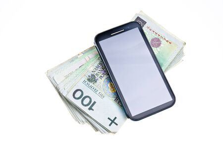 Modern touchscreen cell phone on stack of Polish money photo