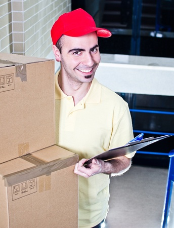Young smiling man working as delivery courier - photo on office stairs Stock Photo - 13215728