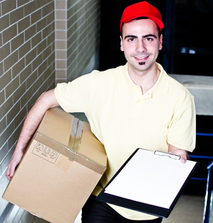 Smiling young courier with package and blank clipboard photo