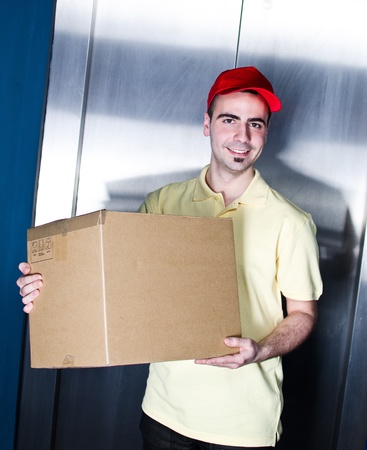 Postman is making a delivery near office elevator Stock Photo - 13215738
