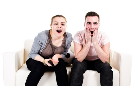 Couple sitting on white sofa and watching scary movie - isolated on white background photo