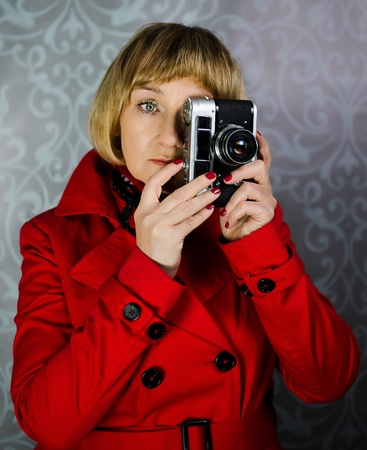 Middle aged lady in red coat taking photos with vintege retro camera photo