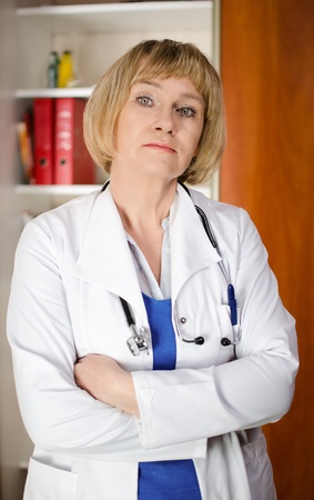 Mature woman doctor in white coat standind in front of shelf with medical files photo