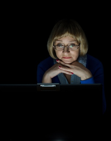 Mature woman working on laptop computer in night