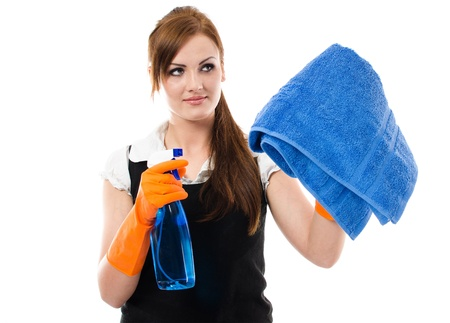 Pretty young woman in orange protective gloves cleaning window with spray and towel Stock Photo