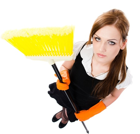 housekeeper: Sexy woman in orange rubber gloves cleaning the house with yellow broom  - isolated on white background Stock Photo