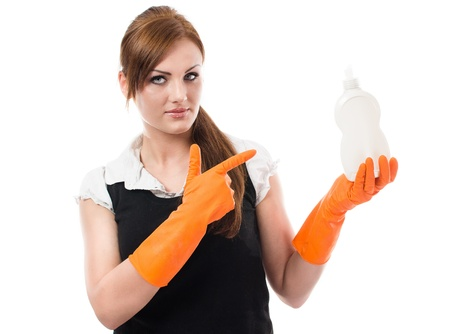 Young woman in orange rubber gloves pointing on dishwashing liquid bottle - isolated on white background photo