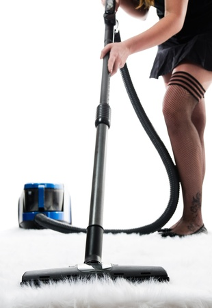 Sexy girl is vacuum cleaning white carpet -  isolated on white background Stock Photo - 13488643