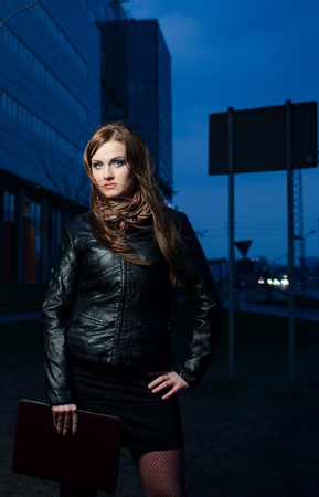Beautiful businesswoman with brown briefcase at night - office building in the background photo