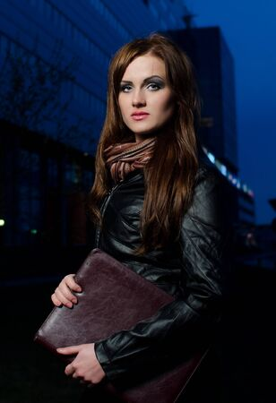 Young businesswoman in big city center at night photo