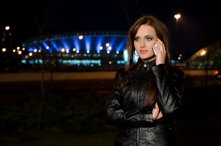 jacked: Beautiful long-haired woman in a black leather jacket talking on a cell phone at night, blurred lights of a big city in the background