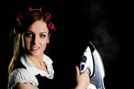 hot rollers: Beautiful woman with curlers on her head holding a steaming iron