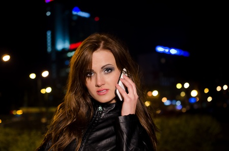 Beautiful business woman talking on a cell phone at night in the middle of the city photo