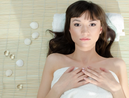 Beautiful dark-haired woman lying on folded white towel in the spa photo