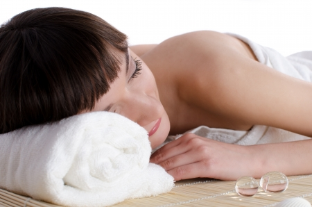 Beautiful dark-haired woman lying in the spa rests on a bamboo mat photo