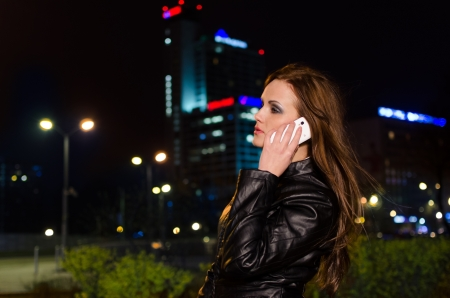 Young brunette woman during phone call in the city centre at night photo