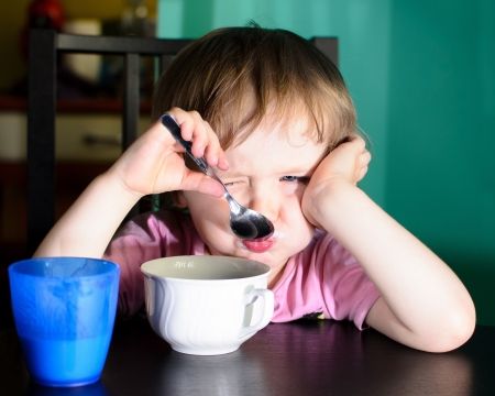 Nervous kleinen Jungen essen und trinken Milch Standard-Bild