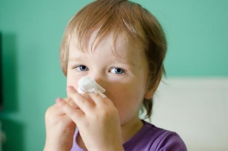 tosiendo: Poco ni�o - ni�o durante la limpieza de la nariz Foto de archivo