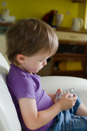 Child playing with medicine pills photo