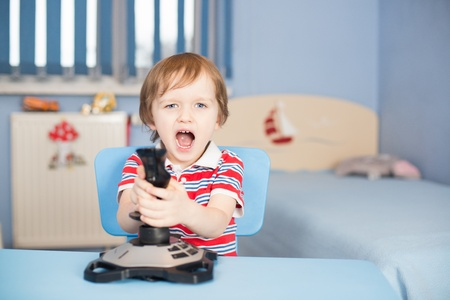 Baby boy screaming when playing computer games with joystick photo